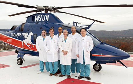 Acute Care and Trauma Surgery team in front of Pegasus Medical transport helicopter.