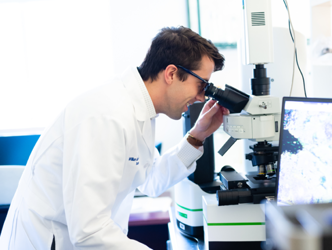 Resident in a lab looking into a microscope