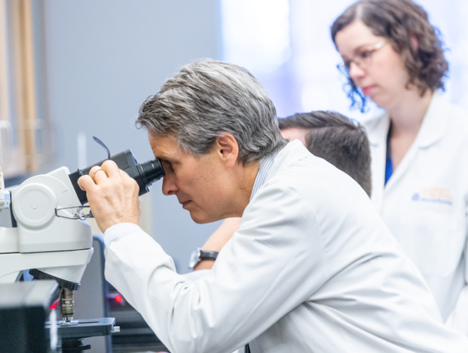 Two residents with a faculty member looking into a microscope