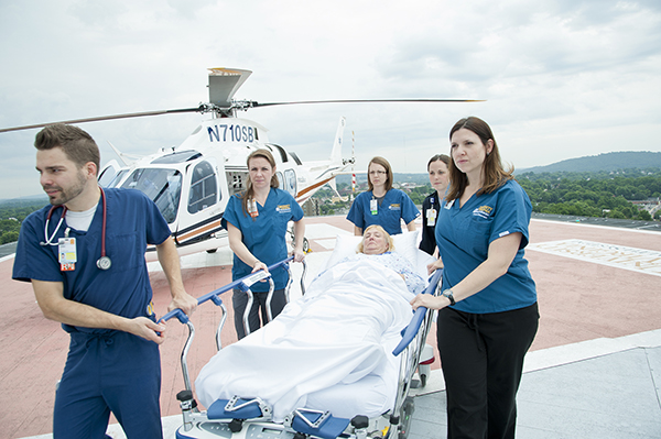 Five hospital employees wheeling a patient in a gurney from the Pegasus helicopter